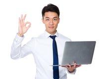 Владение бизнесмена с портативным компьютером и одобренный знак показывать Стоковые Изображения