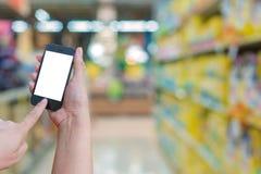 Владение женщины и мобильный телефон экрана касания пока ходящ по магазинам в супер Стоковое фото RF