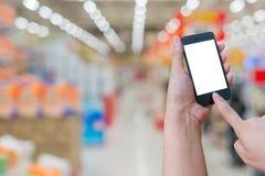 Владение женщины и мобильный телефон экрана касания пока ходящ по магазинам в супер Стоковая Фотография
