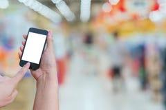 Владение женщины и мобильный телефон экрана касания пока ходящ по магазинам в супер Стоковое Изображение RF