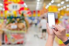Владение женщины и мобильный телефон экрана касания пока ходящ по магазинам в супер Стоковые Фотографии RF