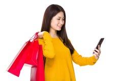 Владение женщины с хозяйственной сумкой и мобильным телефоном Стоковое Изображение