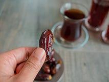Владение плодоовощ даты рукой с турецким чаем Стоковая Фотография