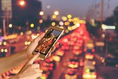 Владение руки женщины и телефон экрана касания умный над запачканным фото автомобиля на дороге с предпосылкой bokeh ligh ночи ули Стоковые Изображения RF