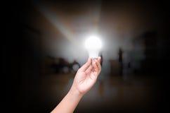 Владение руки женщины освещая шарик СИД на расплывчатой крытой зале offic Стоковая Фотография RF