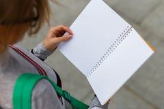 Владения девушки раскрывают тетрадь, взгляд сверху Стоковое Изображение RF
