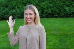 Владения молодой женщины в руках на ключах пальца радуются и смех, s Стоковое Изображение RF