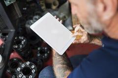Владелец магазина ремонта автомобилей проверяя концепцию таблетки Стоковое фото RF