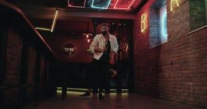 В баре молодой человек в белой куртке танцуя счастливая предпосылка с мелькая цветом освещает акции видеоматериалы
