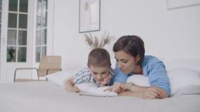 В белой спальне, взгляд мамы и сына на экране и смехе планшета Счастливая семья в кровати в утре читая книгу сток-видео