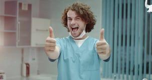 В больнице очень харизматический молодой доктор или хирурги принимают хирургическую маску и усмехаться большие перед акции видеоматериалы