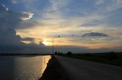 В вечере голубое небо, солнце, сияющий золотой свет за облаками постепенно двигает вниз с взгляда улицы стоковое фото rf