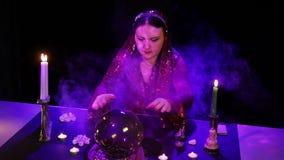В волшебном салоне, цыган читает будущее в волшебном шарике окруженном слепимостью и дымом сток-видео