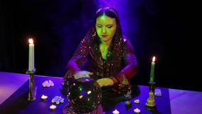 В волшебном салоне, цыган читает будущее в волшебном шарике окруженном слепимостью и дымом акции видеоматериалы