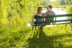 В влюбленности на скамейке в парке Стоковая Фотография RF