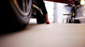 В гараже женщина нося красные высокие пятки выходит автомобиля и прогулок прочь акции видеоматериалы