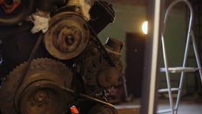 В гараже, мотор ` s автомобиля приостанавливан на кране видеоматериал