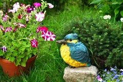 В горшке цветки и скульптура сада птицы стоковая фотография