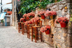 В горшке цветки на каменной стене полностью зацветают с barstools вокруг кафа, Afitos, Halkidiki, Греции стоковые фото