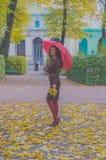 В девушке парка привлекательной с зонтиком и листьями в autum Стоковые Изображения