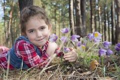 В лесе весной маленькая девочка обнимает цветки к PA стоковое изображение