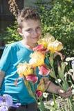 В лете в мальчике сада стоя близко цветки irises Стоковое Изображение RF