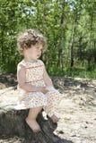 В лете в древесинах маленькая курчавая девушка сидя дальше Стоковые Фото