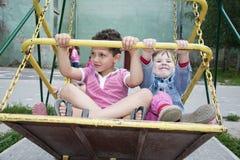 В лете, дети на спортивной площадке на качании Стоковые Изображения