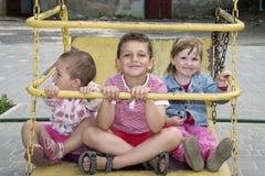 В лете, дети на спортивной площадке на качании Стоковое Фото