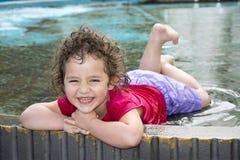 В лете, игра девушки в фонтане в парке Стоковые Изображения