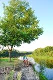 В лете, около реки, на скале, человек сидит с его l Стоковые Фотографии RF