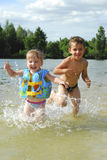 В лете, река потакает мальчику и девушка, они заразительные поднимающие вверх Стоковые Изображения RF