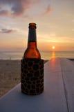 В летних каникулах. Бутылка пива на пляже на заходе солнца стоковое изображение