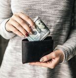 В женщинах руки ` s кожаный бумажник с валюшкой 100 долларов Предложение дела красивейший manicure Стоковое Изображение