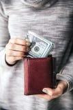 В женщинах руки ` s коричневый кожаный бумажник с валюшкой 100 долларов Предложение дела красивейший manicure Стоковая Фотография