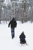 В зиме, отец носит его сына на скелетоне в древесинах стоковое фото