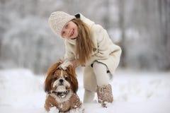 В зиме, снег падает в снежный лес, игру маленькой девочки с собакой стоковые фото