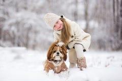 В зиме, снег падает в снежный лес, игру маленькой девочки с собакой стоковая фотография
