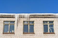 В зиме сосульки висят на крыше здания Стоковое Изображение