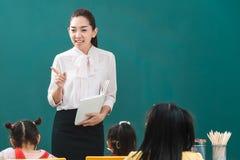 В классе, азиатский учитель учит студенту стоковые изображения