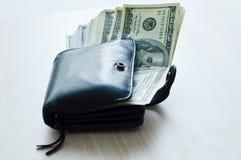 В коже черноты бумажник много деньги Стоковая Фотография