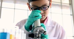 В комнате лаборатории, взгляд мальчика через микроскоп акции видеоматериалы