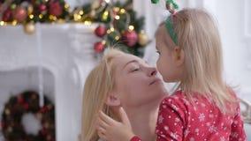 В комнате украшенной с украшениями рождества, женщина держит ее маленькую дочь в ее оружиях и целует ее на сток-видео