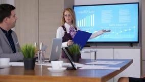 В конференц-зале коммерсантка с доской сзажимом для бумаги в руках представляет данные компании сток-видео
