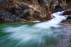 В красивом зеленом лесе на огромных утесах быстрый tempestuous водопад горы пропускает Стоковая Фотография