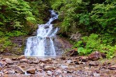 В красивом зеленом лесе на огромных утесах быстрый tempestuous водопад горы пропускает Стоковая Фотография RF