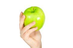 В красивых руках зеленое яблоко, изолированное на белой предпосылке Стоковое Изображение