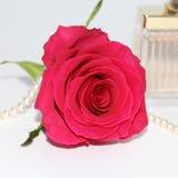 В красных розах, духах, и жемчугах фото одного стоковое фото rf