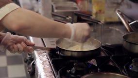 В кухне кашевар добавляет сырцовое яичко к макаронным изделиям с мясом на горящей плите акции видеоматериалы