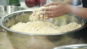 В кухне, шеф-повар изнашивает тесто рук в большой шар металла видеоматериал